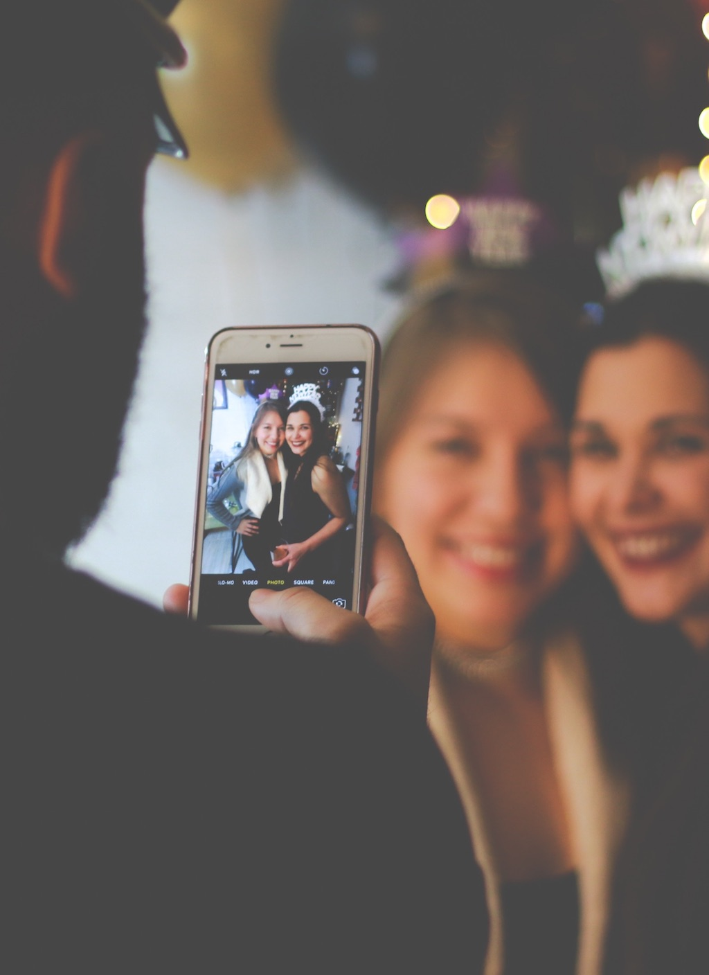 taking a photo of two girl with a cell phone